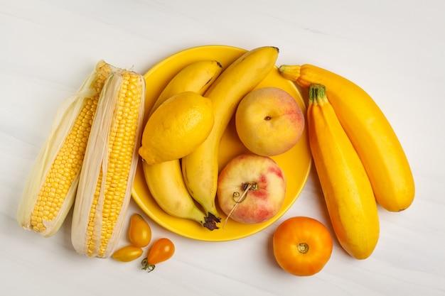 Variedade de vegetais amarelos no fundo branco, vista superior. frutas e vegetais contendo caroteno. Foto Premium