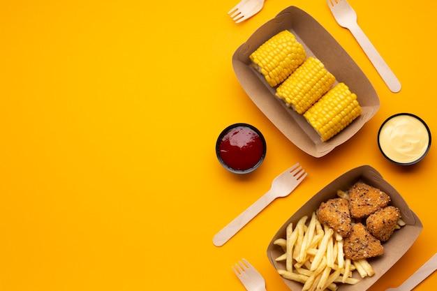 Variedade de vista superior com batatas fritas, crocante e milho Foto gratuita