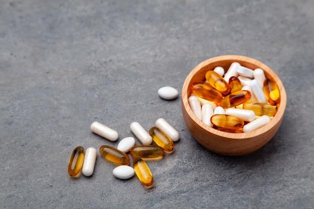 Variedade de vitaminas de medicamentos farmacêuticos, pílulas, cápsulas moles em uma tigela de madeira no fundo cinza Foto Premium