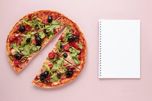 Variedade plana leiga com pizza e notebook Foto gratuita