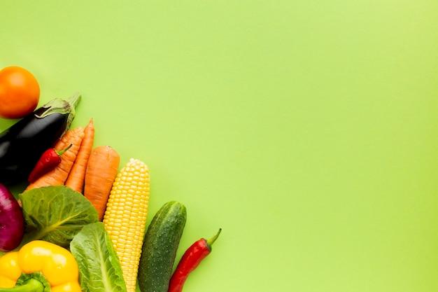 Variedade plana leiga de vegetais sobre fundo verde, com espaço de cópia Foto gratuita