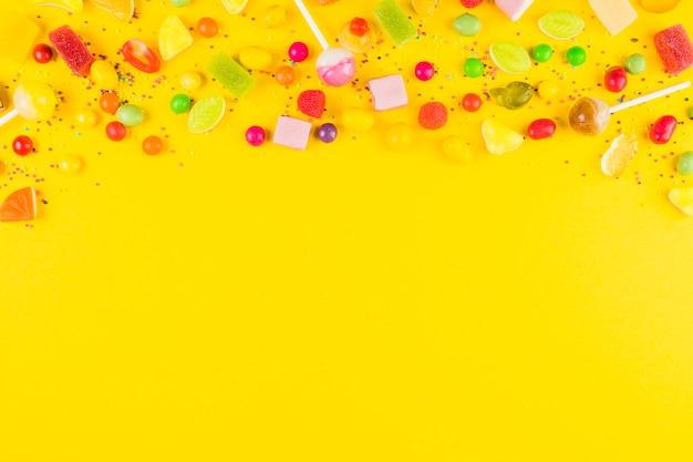 Variedades de doces doces coloridos na superfície amarela Foto gratuita
