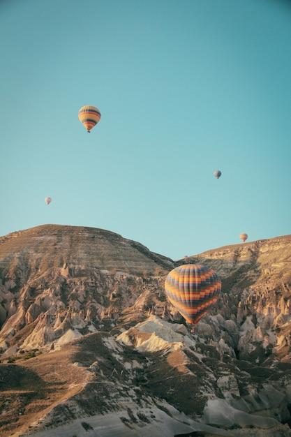 Vários balões de ar quente coloridos flutuando sobre montanhas Foto gratuita