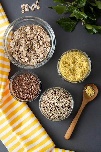 Vários cereais não cozidos. tipos diferentes de aveia em flocos em umas bacias no fundo cinzento. Foto Premium
