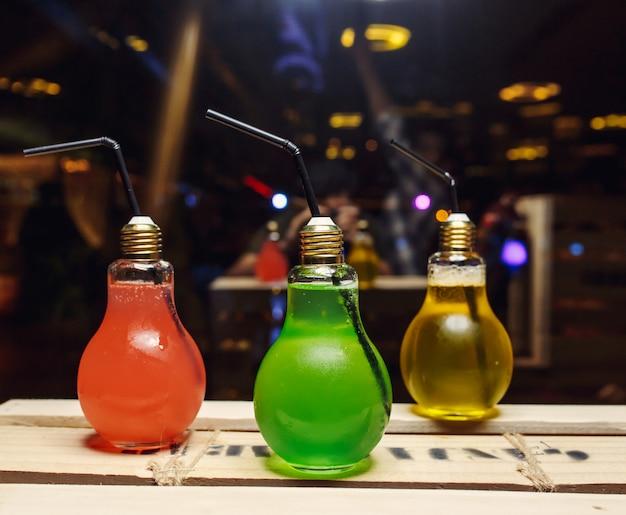 Vários cocktails de cor em garrafas de lâmpada Foto gratuita