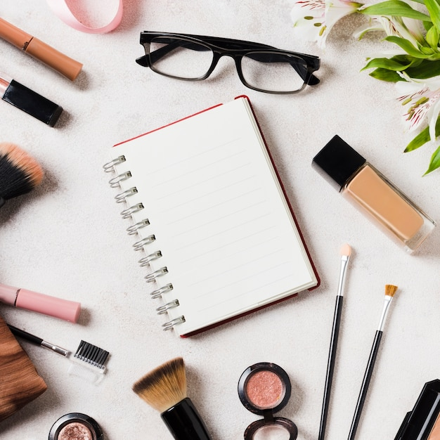 Vários cosméticos e óculos espalhados em torno do caderno em branco Foto gratuita