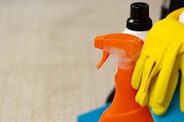 Vários detergentes de limpeza doméstica e garrafas em um balde de plástico no chão Foto Premium