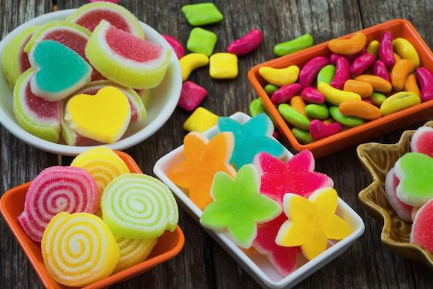 Vários doces açucarados coloridos no recipiente na prancha de madeira velha Foto Premium
