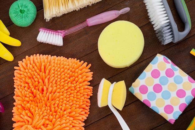 Vários equipamentos de limpeza dispostos no piso de madeira Foto Premium
