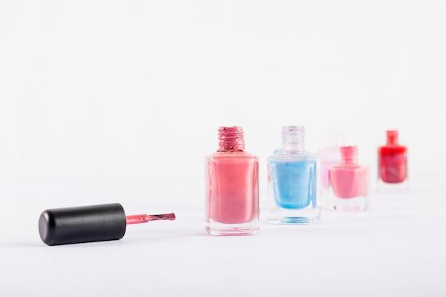 Vários frascos de esmaltes coloridos, isolados no fundo branco Foto gratuita