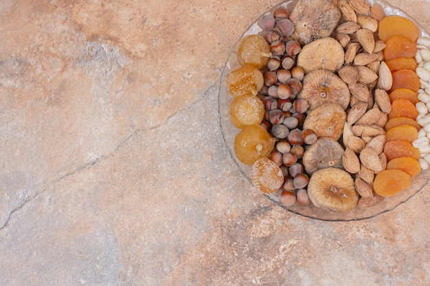 Vários frutos secos e nozes na placa de vidro. Foto gratuita