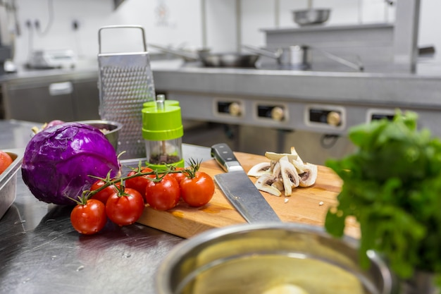 Vários legumes e utensílios de cozinha em uma mesa de cozinha em um restaurante Foto Premium