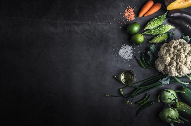 Vários legumes em uma mesa preta com espaço para uma mensagem para escrever Foto Premium