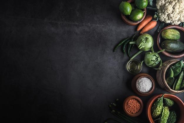 Vários legumes em uma mesa preta com espaço para uma mensagem Foto Premium