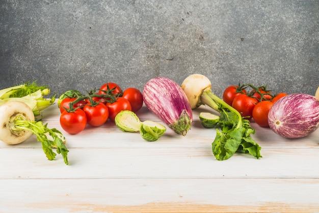 Vários legumes frescos dispostos na mesa de madeira Foto gratuita