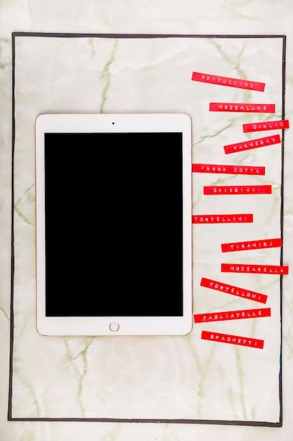 Vários menus ao lado de tablet digital com tela preta em branco Foto gratuita