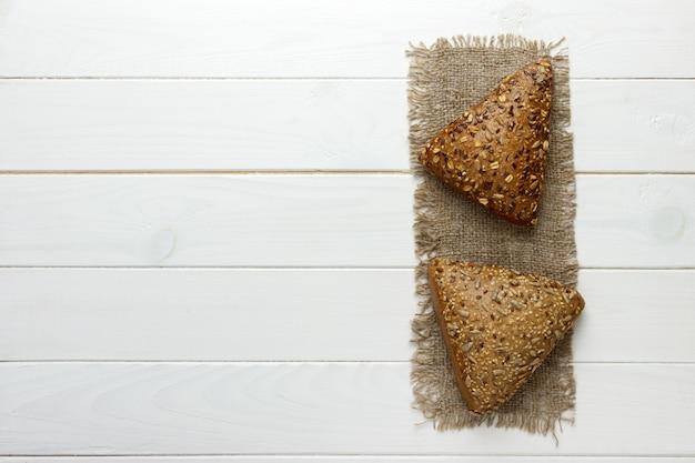 Vários, pequeno, multi, grão, triangular, dado forma, pão, polvilhado, com, inteiro, sementes girassol, linho, e, sementes gergelim, ligado, um, sackcloth Foto Premium