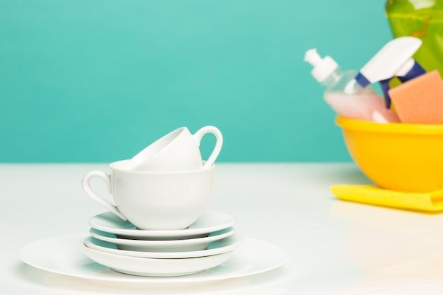 Vários pratos, esponjas de cozinha e garrafas de plástico com sabão líquido para lavar louça Foto gratuita