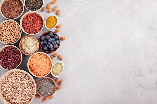 Vários superalimentos, vegan, conceito de produtos orgânicos da dieta saudável vegetariana Foto Premium
