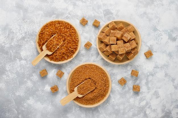 Vários tipos de açúcar mascavo no concreto, vista superior Foto gratuita