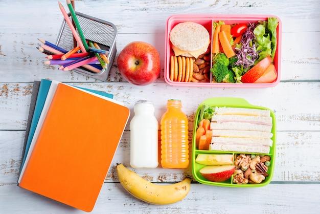 Vários tipos de lancheiras saudáveis de sanduíche. kid bento pack para escola conjunto em pacote plástico, banana e maçã com suco de laranja, leite. Foto Premium