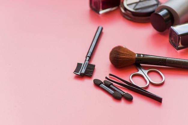 Vários tipos de pincéis de maquiagem; produto de tesoura e cosméticos em fundo rosa Foto gratuita