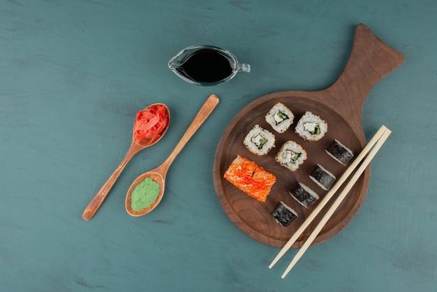 Vários tipos de prato de rolo de sushi com gengibre em conserva, wasabi e molho de soja na mesa azul. Foto gratuita