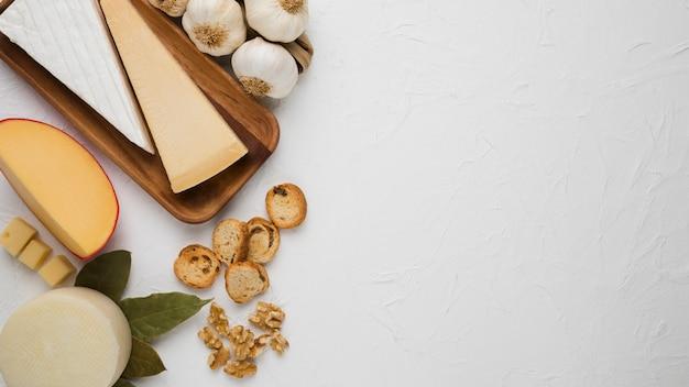 Vários tipos de queijo com fatia de pão; noz; alho e folhas de louro sobre o pano de fundo branco Foto gratuita