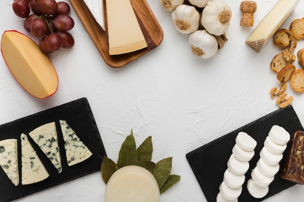 Vários tipos de queijo com uvas saborosas e ingrediente em fundo branco Foto gratuita