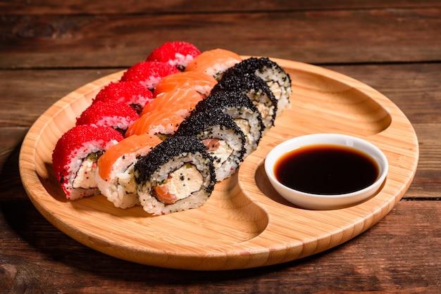 Vários tipos de sushi servido. rolo com salmão, abacate, pepino. menu de sushi. comida japonesa Foto Premium