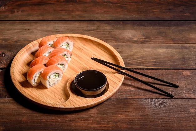 Vários tipos de sushi serviram em um escuro. rolo com salmão, abacate, pepino. menu de sushi. comida japonesa Foto Premium