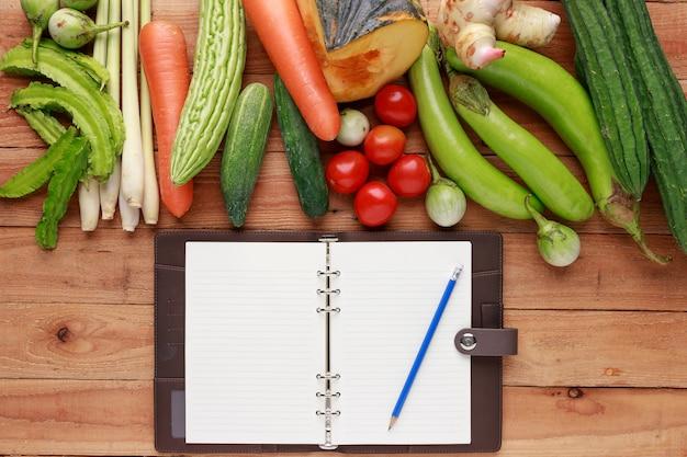 Vários vegetais com caderno em branco e lápis sobre fundo de madeira. vista do topo Foto Premium