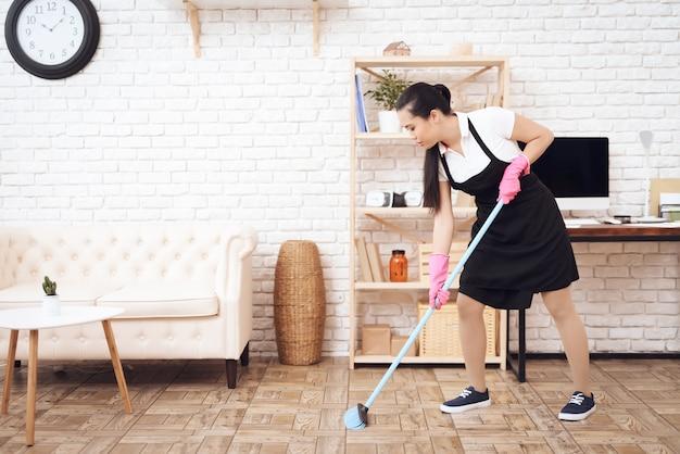 Varrer o chão com o serviço de limpeza da vassoura. Foto Premium