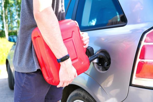 Vasilha vermelha nas mãos de um homem. encher um carro parado com gasolina de uma lata. Foto Premium