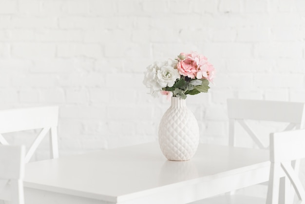 Vaso branco de florescência na tabela contra a parede de tijolo Foto gratuita