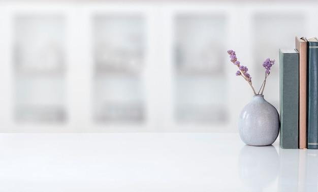 Vaso cerâmico da maquete da planta de casa com o livro na tabela superior branca na sala moderna. copie o espaço. Foto Premium