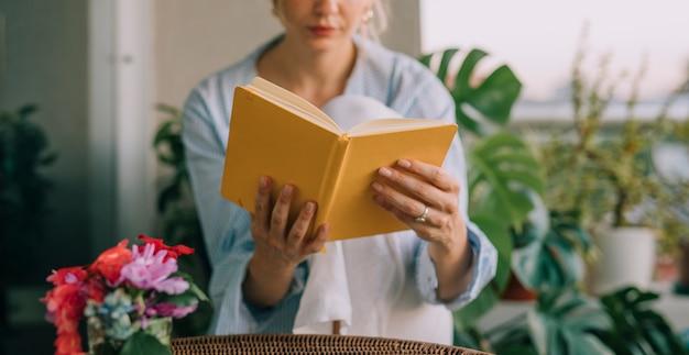 Vaso de flor na frente da jovem mulher lendo o livro amarelo Foto gratuita