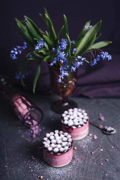 Vaso de flor roxa com dois delicioso bolo de queijo no fundo da textura de pedra Foto gratuita