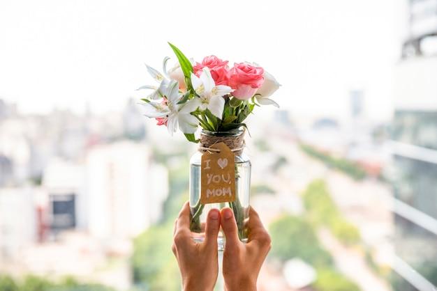 Vaso de flores para o dia da mãe nas mãos Foto gratuita