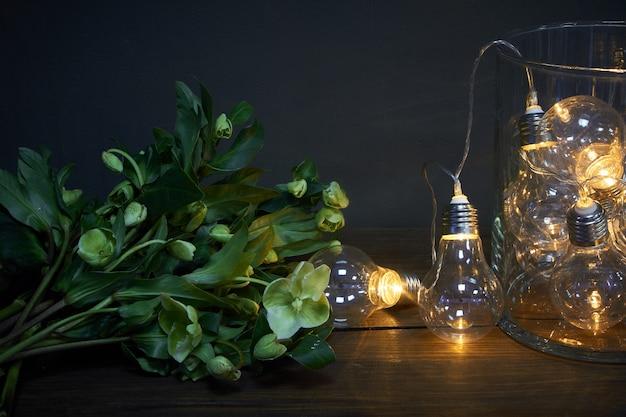 Vaso de vidro cheio de lâmpadas luminosas e um buquê de heléboro Foto Premium