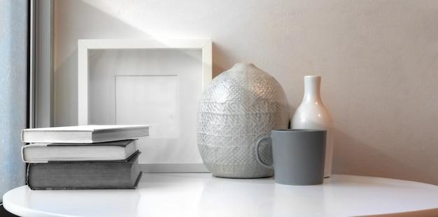 Vasos de cerâmica e mock up frame na mesa branca em espaço de trabalho mínimo Foto Premium