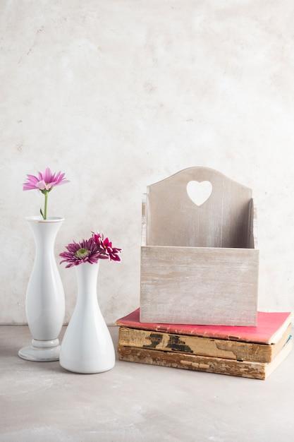Vasos de flores e caixa de cartão postal em livros colocados na mesa Foto gratuita