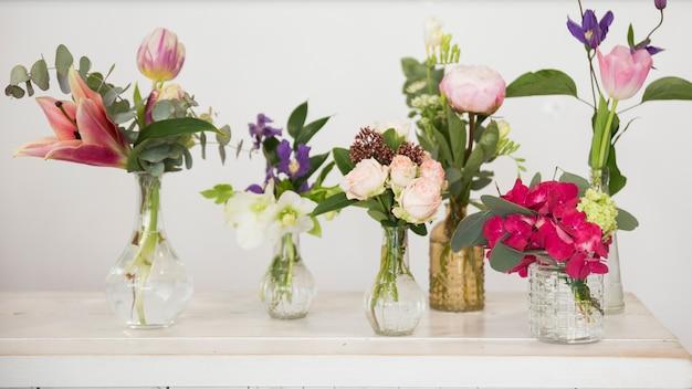Vasos de flores frescas na mesa contra o pano de fundo branco Foto gratuita