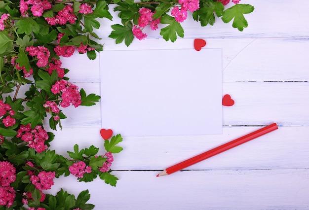 Vazia folha de papel e um lápis de madeira vermelho sobre uma superfície branca Foto Premium