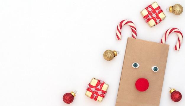 Veado de natal feito de bolsa artesanal e duas bengalas de natal com caixas de presente, bolas vermelhas e douradas sobre fundo branco. estilo liso leigo com espaço de cópia. Foto Premium