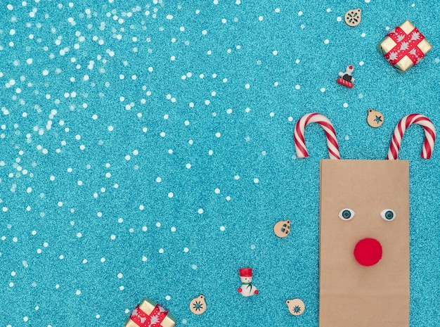 Veado de natal feito de bolsa artesanal e duas bengalas de natal com duas caixas de presente e enfeites de madeira em fundo azul com neve branca. cartão de felicitações Foto Premium