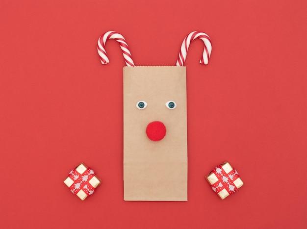 Veado de natal feito de sacola artesanal e duas bengalas de natal com caixas de presente Foto Premium