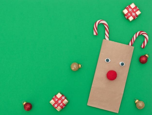 Veado de natal feito de sacola de compras de artesanato e duas bengalas de natal com caixas de presente e bolas de natal em fundo verde. estilo liso leigo com espaço de cópia. Foto Premium