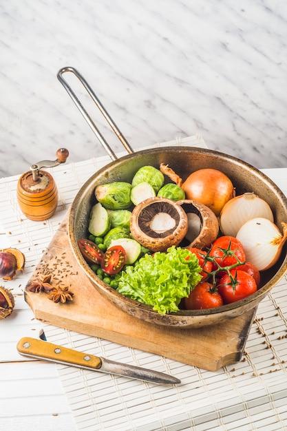 Vegetais crus em pan vintage velho sobre a tábua de cortar Foto gratuita