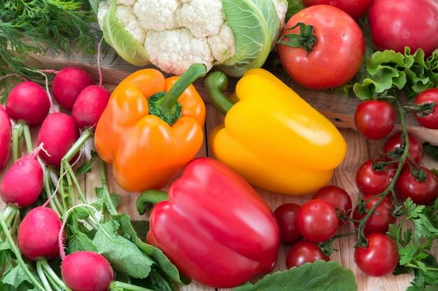 Vegetais diferentes como tomate, couve-flor, pimentos, rabanetes, tomates cereja Foto Premium